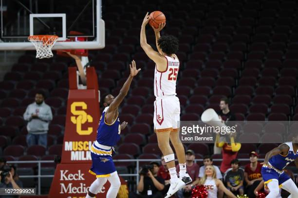 Bennie Boatwright of the USC Trojans shoots a threepointer against James Suber of the Cal State Bakersfield Roadrunners during a college basketball...