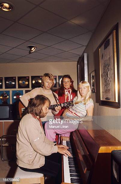 Benny Andersson playing piano accompanied on guitar by Bjorn Ulvaeus in the presence of their wives Agnetha Faltskog and Anni-Frid Lyngstad in a room...