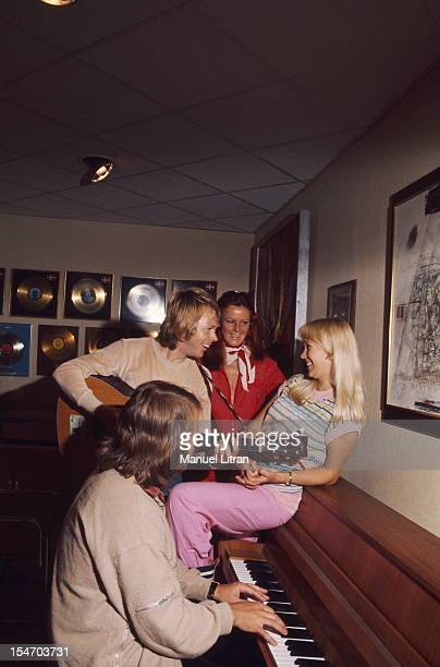 Benny Andersson playing piano accompanied on guitar by Bjorn Ulvaeus in the presence of their wives Agnetha Faltskog and AnniFrid Lyngstad in a room...