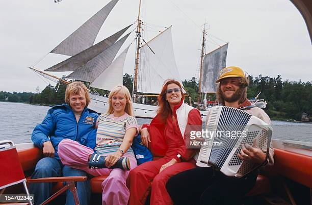Benny Andersson playing the accordion sitting in the back of a boat to the dimensions of his wife Anni-Frid Lyngstad and Bjorn Ulvaeus with his wife...