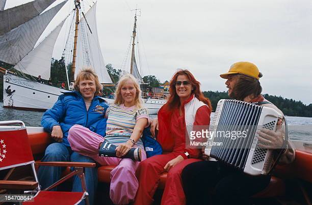 Benny Andersson playing the accordion sitting in the back of a boat to the dimensions of his wife AnniFrid Lyngstad and Bjorn Ulvaeus with his wife...
