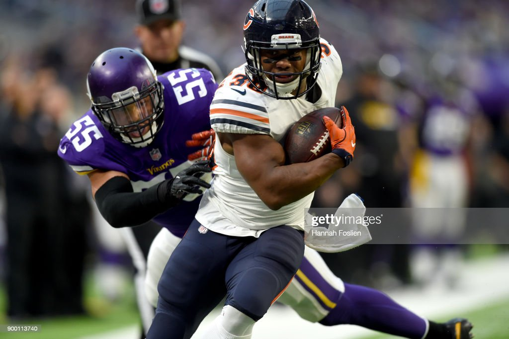 Benny Cunningham #30 of the Chicago Bears carries the ball while being pursued by defender Anthony Barr #55 of the Minnesota Vikings in the fourth quarter of the game on December 31, 2017 at U.S. Bank Stadium in Minneapolis, Minnesota.