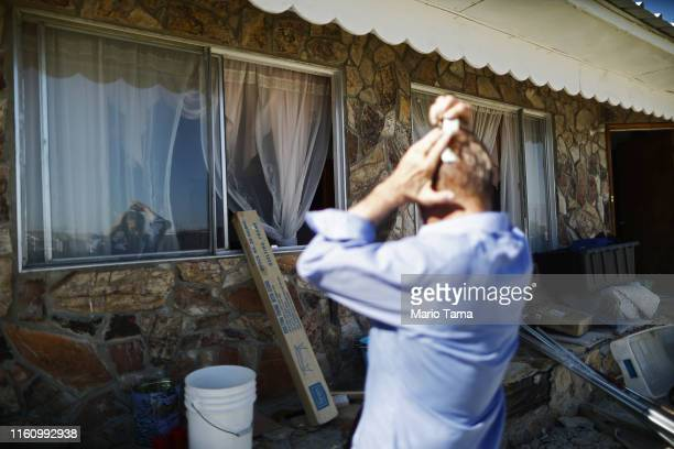 Benny Eldridge comb his hair using a window as a mirror in front his home which has been deemed uninhabitable due to structural damage from the...