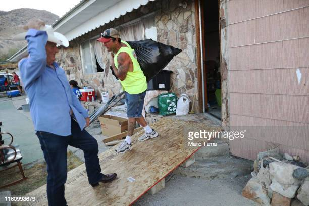 Benny Eldridge looks on as soninlaw Johnnie Jackson removes trash from his home which has been deemed uninhabitable due to structural damage from the...