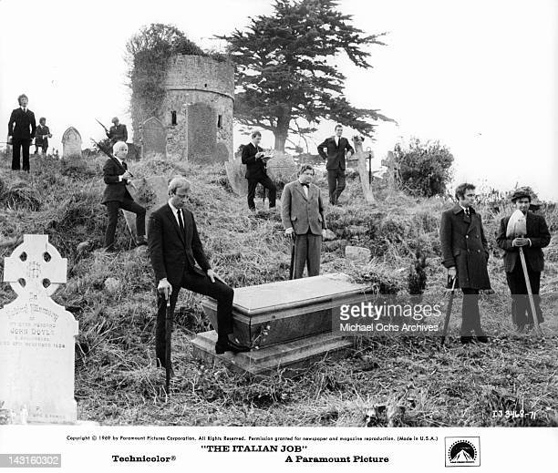 Benny Hill standing among other men with coffin at cemetery in a scene from the film 'The Italian Job' 1969