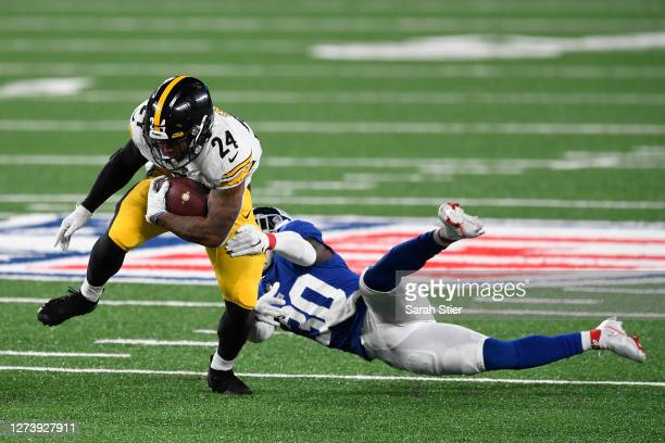 Benny Snell Jr. #24 of the Pittsburgh Steelers carries the ball past the defense of Darnay Holmes of the New York Giants during the first half at...