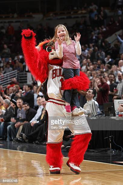 Benny the Bull mascot of the Chicago Bulls holds up a young fan during the game against the Miami Heat at the United Center on February 12 2009 in...