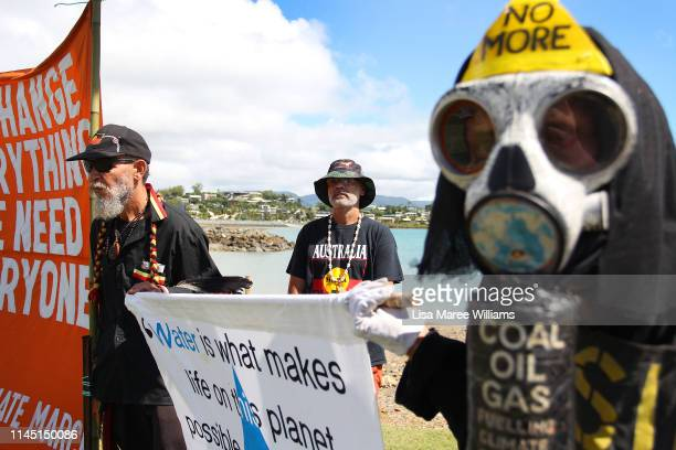Benny Zable a performance artist for peace and environment and activists stand at the edge of Airlie Bay during a anti Adani Carmichael Coal Mine...