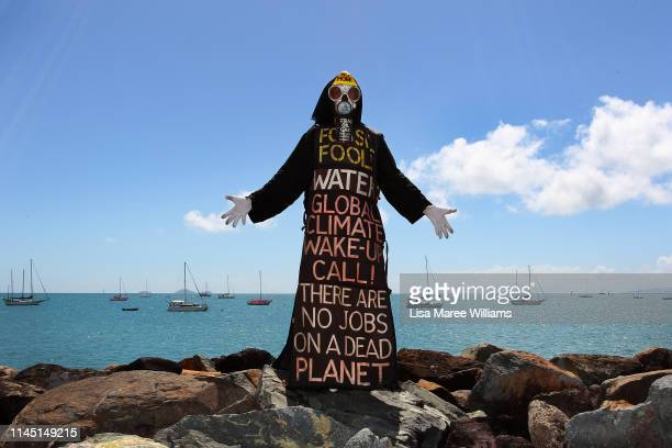 Benny Zable a performance artist for peace and environment stands in costume at the edge of Airlie Bay during a anti Adani Carmichael Coal Mine rally...