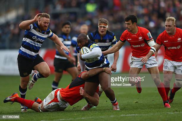 Beno Obano of Bath powers his way through the challenge of Schalk Burger of Saracens during the Aviva Premiership match between Bath Rugby and...