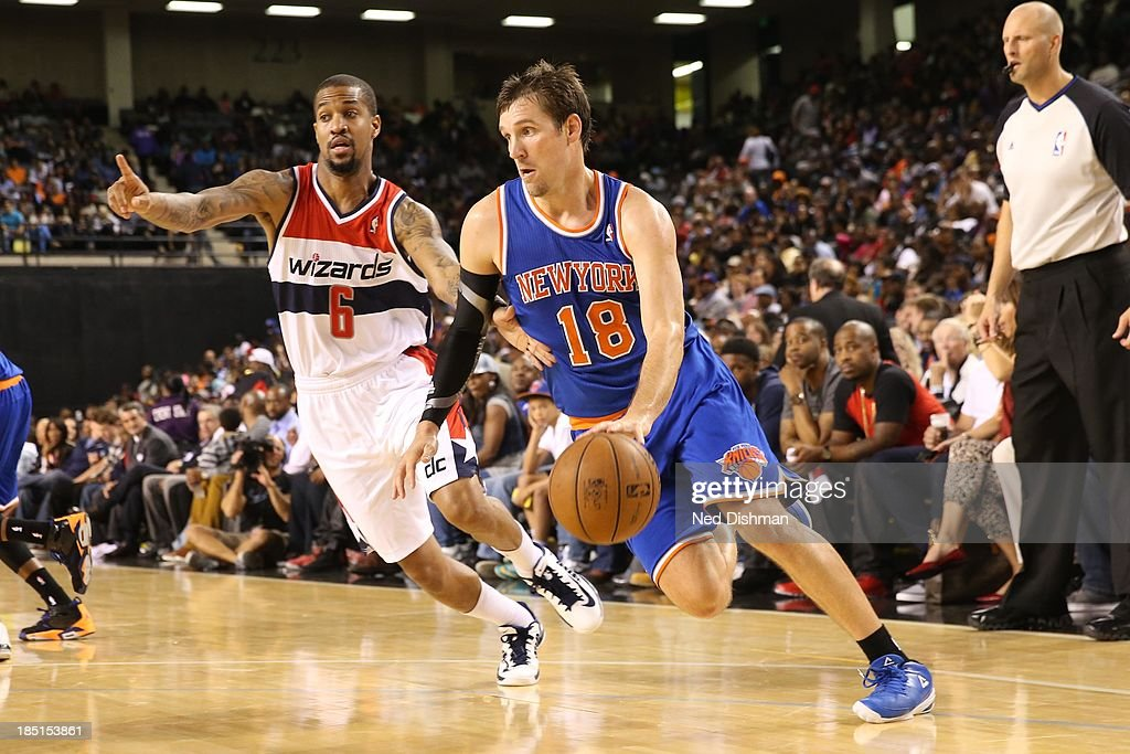 Beno Udrih #18 of the New York Knicks drives against Eric Maynor #6 of the Washington Wizards during the pre-season game at the Baltimore Arena on October 17, 2013 in Baltimore, MD.