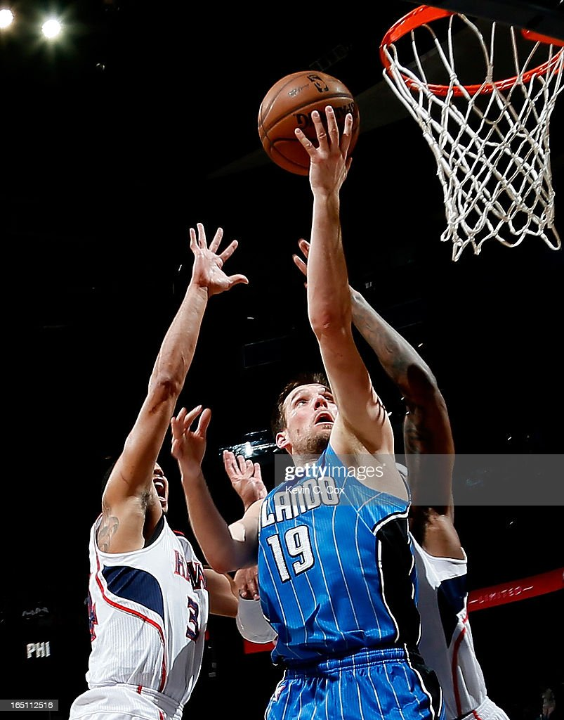 Beno Udrih #19 of the Orlando Magic lays in a basket against Devin Harris #34 and Josh Smith #5 of the Atlanta Hawks at Philips Arena on March 30, 2013 in Atlanta, Georgia.
