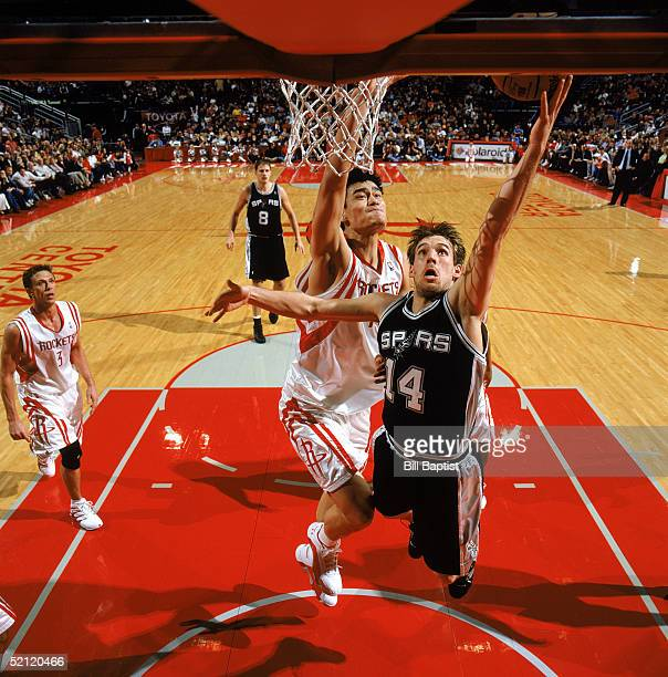 Beno Udrih of the San Antonio Spurs lays up a shot against Yao Ming of the Houston Rockets during the game at Toyota Center on January 15 2005 in...