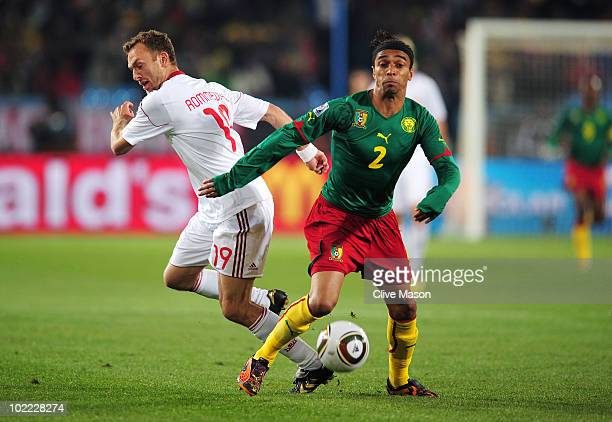 Benoit AssouEkotto of Cameroon and Dennis Rommedahl of Denmark battle for the ball during the 2010 FIFA World Cup South Africa Group E match between...