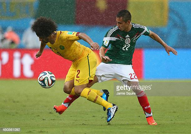 Benoit AssouEkotto of Cameroon and Paul Aguilar of Mexico battle for the ball during the 2014 FIFA World Cup Brazil Group A match between Mexico and...