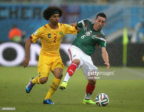 Benoit AssouEkotto of Cameroon battles with Hector Herrera of Mexico during the 2014 FIFA World Cup Brazil Group A match between Mexico and Cameroon...