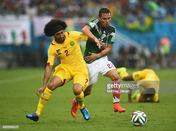 Benoit AssouEkotto of Cameroon holds off Paul Aguilar of Mexico in the first half during the 2014 FIFA World Cup Brazil Group A match between Mexico...
