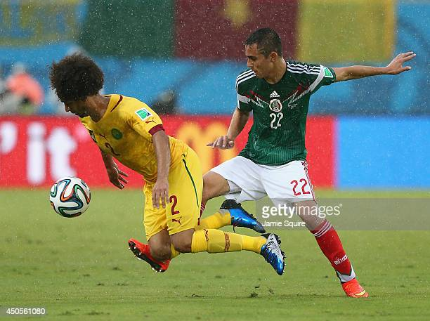 Benoit AssouEkotto of Cameroon is challenged by Paul Aguilar of Mexico during the 2014 FIFA World Cup Brazil Group A match between Mexico and...