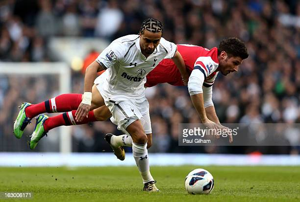 Benoit AssouEkotto of Spurs and Olivier Giroud of Arsenal compete for the ball during the Barclays Premier League match between Tottenham Hotspur and...
