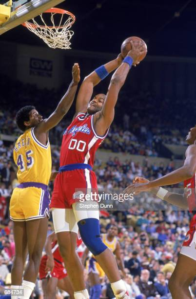 Benoit Benjamin of the Los Angeles Clippers shoots the ball over AC Green of the Los Angeles Lakers during the NBA game at the Great Western Forum in...