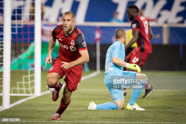 Benoit Cheyrou of Toronto FC comes over to teammates to celebrate the goal that ties the match while goalkeeper Luis Robles 31 gets up from missing...
