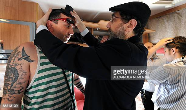 Benoit FINCKE Russian Rabbis Boroukh Kleinberg and Chaim Manklin hold phylacteries on people's heads inside their Mitzvah Bus in Moscow on June 16...