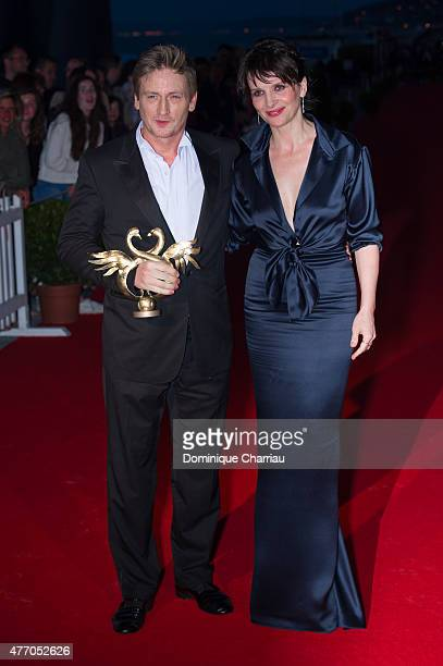 Benoit Magimel poses with actress Juliette Binoche as he awarded best actor during the closing ceremony of the 29th Cabourg Film Festival on June 13...