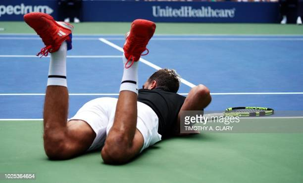 Benoit Paire of France falls on court against Roger Federer of Switzerland on Day 4 of the 2018 US Open Men's Singles match at the USTA Billie Jean...
