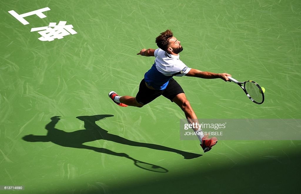 TOPSHOT - Benoit Paire of France hits a return against Joao Sousa of Portugal during their first round men's singles match at the Shanghai Masters tennis tournament in Shanghai on October 10, 2016. / AFP / JOHANNES