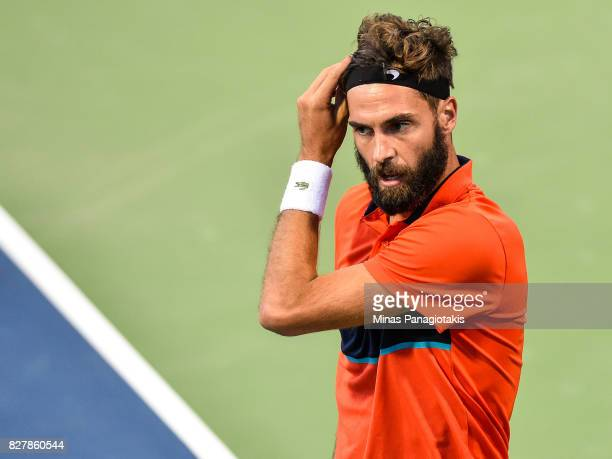 Benoit Paire of France looks on as he adjusts his head band against Jared Donaldson of the United States during day five of the Rogers Cup presented...