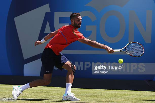 Benoit Paire of France plays a backhand against Jarkko Nieminen of Finland during their Men's Singles match on day two of the Aegon Championships at...