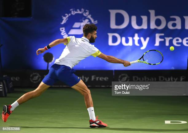 Benoit Paire of France plays a backhand during his match against Roger Federer of Switzerland on day two of the ATP Dubai Duty Free Tennis...
