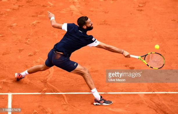 Benoit Paire of France plays a backhand during his mens singles fourth round match against Kei Nishikori of Japan during Day nine of the 2019 French...