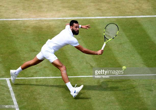 Benoit Paire of France plays a backhand in his Men's Singles fourth round match against Roberto Bautista Agut of Spain during Day Seven of The...