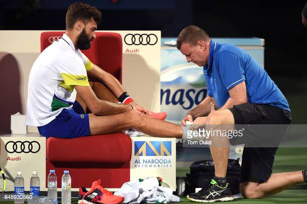 Benoit Paire of France receives medical treatment during his match against Roger Federer of Switzerland on day two of the ATP Dubai Duty Free Tennis...