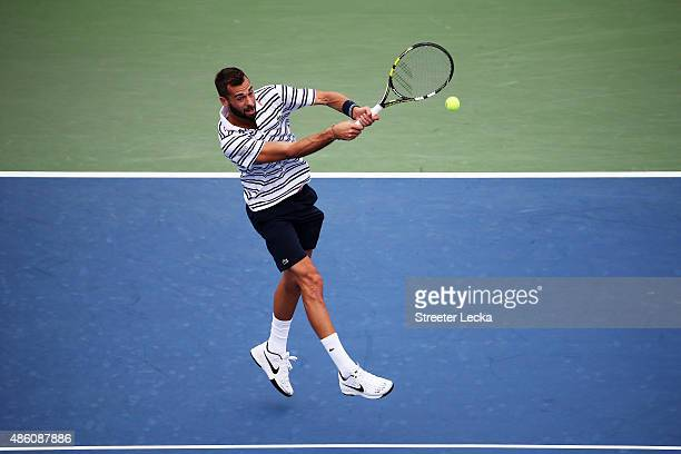 Benoit Paire of France returns a shot to Kei Nishikori of Japan during their men's first round match on Day One of the 2015 US Open at the USTA...