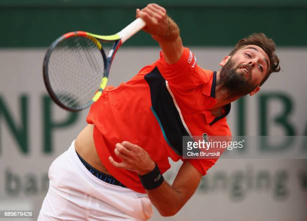 Benoit Paire of France serves during the mens singles first round match against Rafael Nadal of Spain on day two of the 2017 French Open at Roland...