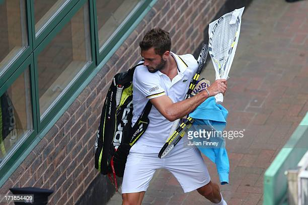 Benoit Paire of France smashes one of his racquets against a wall as he leaves Court 18 following his defeat to Lukasz Kubot of Poland during their...