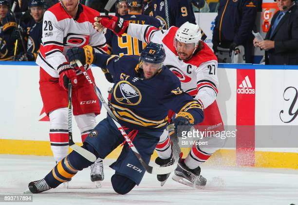 Benoit Pouliot of the Buffalo Sabres is upended by Justin Faulk of the Carolina Hurricanes during an NHL game on December 15 2017 at KeyBank Center...