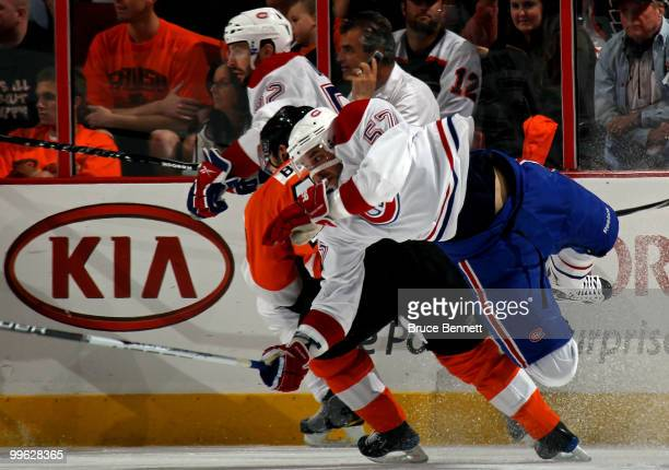 Benoit Pouliot of the Montreal Canadiens gets knocked off his skates against Danny Briere of the Philadelphia Flyers in Game 1 of the Eastern...