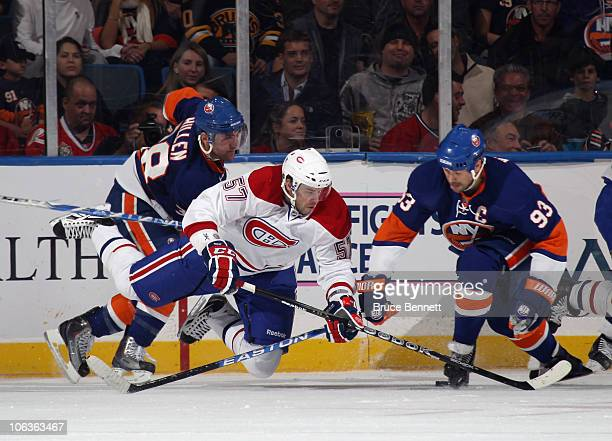 Benoit Pouliot of the Montreal Canadiens is tripped up by Jack Hillen and Doug Weight of the New York Islanders at the Nassau Coliseum on October 29...