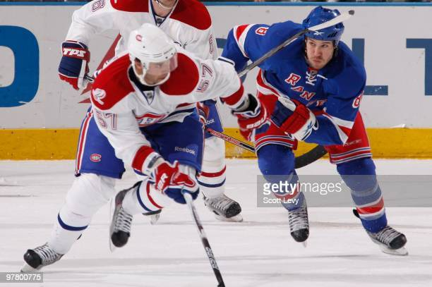 Benoit Pouliot of the Montreal Canadiens races for the puck under pressure by Brandon Prust of the New York Rangers on March 16 2010 at Madison...