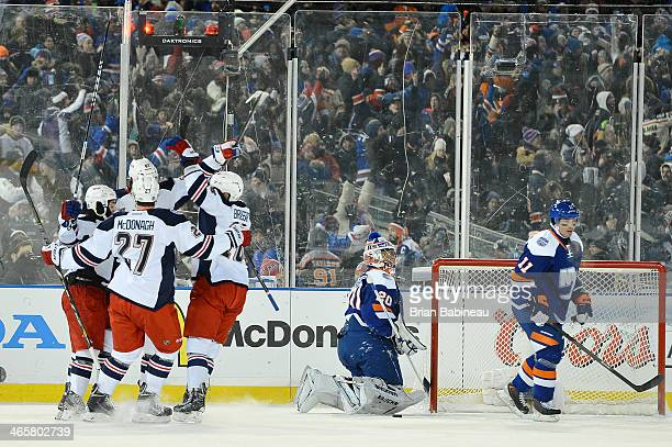 Benoit Pouliot of the New York Rangers celebrates with teammates after scoring against the New York Islanders in the second period to tie the game...