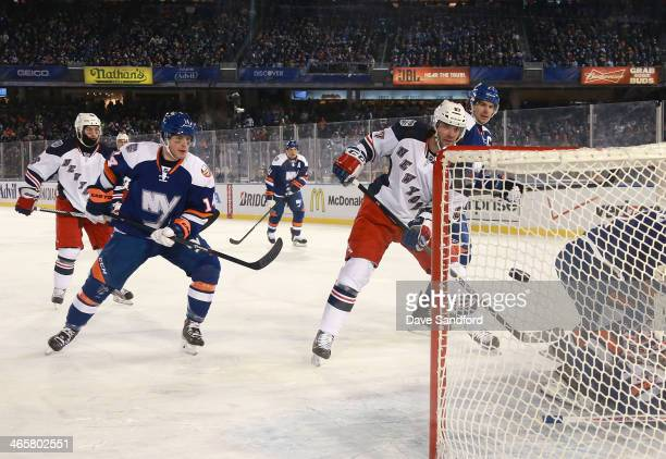 Benoit Pouliot of the New York Rangers scores in the second period as Thomas Hickey of the New York Islanders looks on during the 2014 Coors Light...