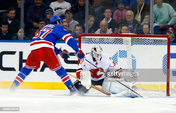 Benoit Pouliot of the New York Rangers scores the shoot out winning goal against Karri Ramo of the Calgary Flames at Madison Square Garden on...