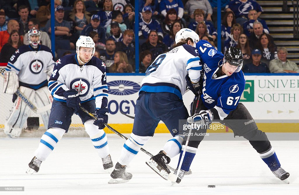 Benoit Pouliot #67 of the Tampa Bay Lightning is hit by Alex Burmistrov #8 of the Winnipeg Jets during the second period of the game at the Tampa Bay Times Forum on February 1, 2013 in Tampa, Florida.