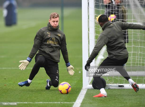 Benrd Leno saves vrom Ainsley Maitland-Niles Bernd Leno of Arsenal during a training session at London Colney on November 24, 2018 in St Albans,...