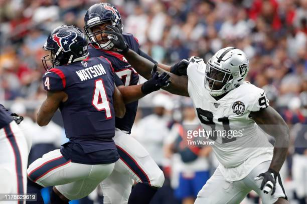 Benson Mayowa of the Oakland Raiders pressures Deshaun Watson of the Houston Texans in the second quarter at NRG Stadium on October 27, 2019 in...
