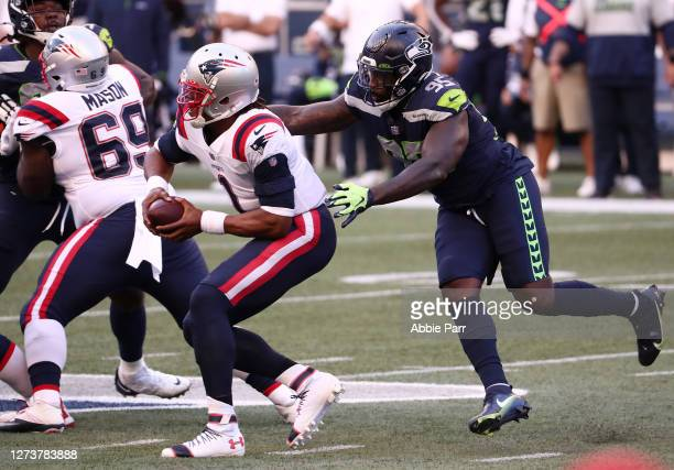 Benson Mayowa of the Seattle Seahawks attempts to tackle Cam Newton of the New England Patriots during the first half at CenturyLink Field on...
