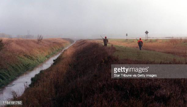 Benson, Mn., Sat., Oct. 13, 2001--Fog envelops hunters as the 2001 Minnesota pheasant season opens. IN THIS PHOTO: Through the wet grass and early...